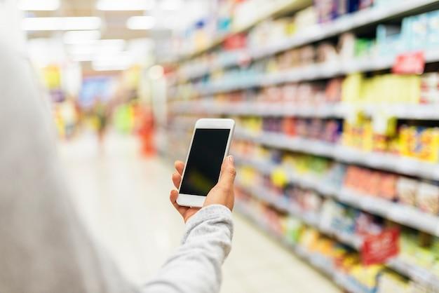 Close up van vrouw met behulp van haar mobiel in de supermarkt. marktvoedselconcept.