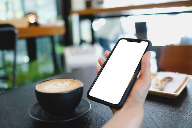 Close up van vrouw met behulp van mobiele blanco slimme telefoon en creditcard die massages verzendt in de coffeeshop