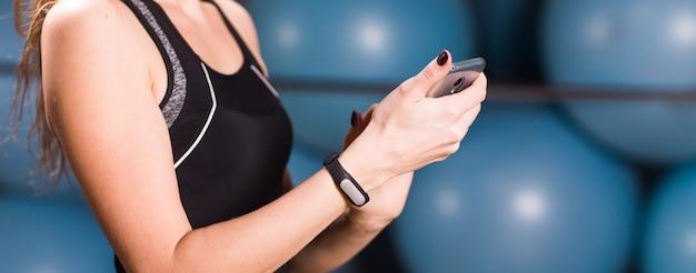 Close up van vrouw met behulp van mobiele telefoon en fitness tracker in sportschool