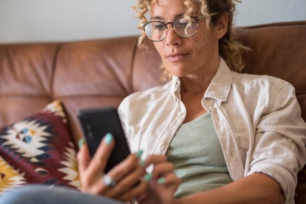 Close up van vrouw met behulp van moderne slimme telefoon thuis zittend op de bank genieten van internetverbinding draadloze vrouwelijke mensen met toepassing op mobiel schrijven of lezen van e-mailmeldingen