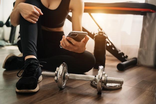 Close up van vrouw met behulp van slimme telefoon tijdens het trainen in de fitnessruimte. sport en technologie concept. leefstijlen en gezondheidszorg thema. in het ochtendlicht