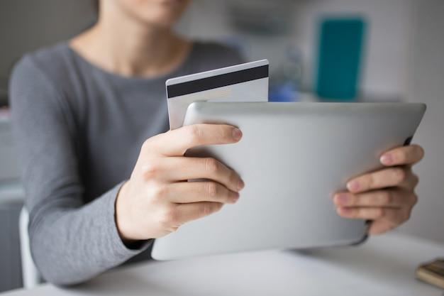 Close-up van vrouw met behulp van tablet en creditcard