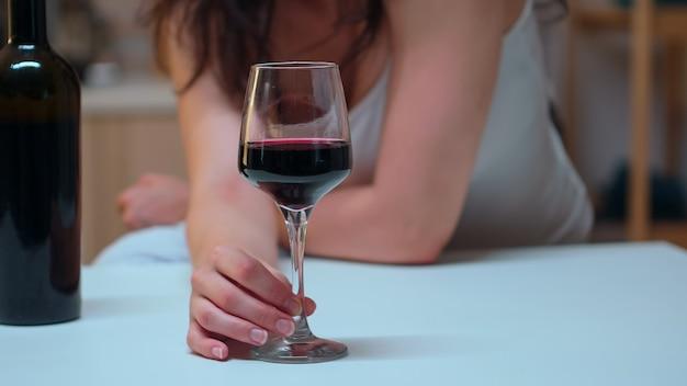 Close up van vrouw met een glas rode wijn op tafel. ongelukkige persoon die lijdt aan migraine, depressie, ziekte en angst zich uitgeput voelen met symptomen van duizeligheid met alcoholismeproblemen.