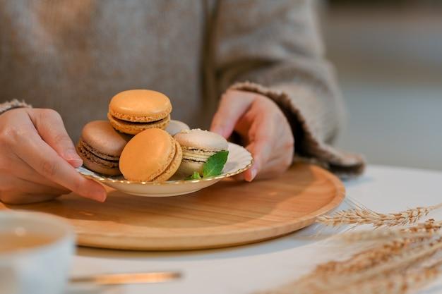 Close-up van vrouw met een plaat van franse kleurrijke macarons uit houten dienblad op koffietafel