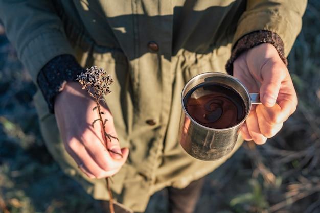 Close up van vrouw met kopje koffie en bloem in prachtig zonlicht. schoonheid in de natuur concept: vrouwelijke handen houden kopje warme drank en een droge veldbloem.
