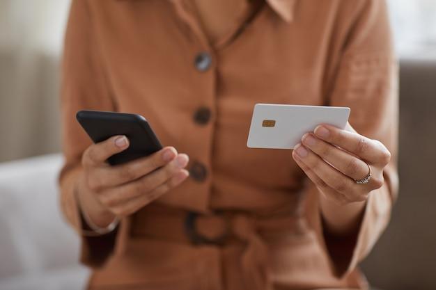 Close-up van vrouw met mobiele telefoon en creditcard in haar handen die ze online betaalt voor rekeningen