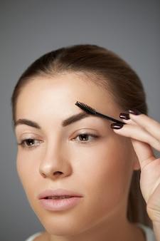 Close-up van vrouw mooie perfect gevormde wenkbrauw, lange wimpers met professionele make-up en wenkbrauwborstel. jong vrouwelijk model dat bruine wenkbrauwen vormgeeft.