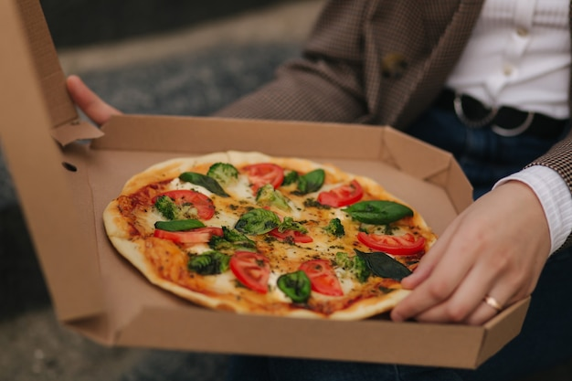 Close up van vrouw open pizzadoos buitenshuis