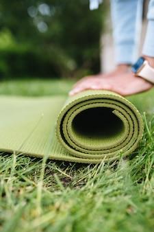 Close-up van vrouw roll fitness of yoga mat vouwen na het trainen in het park