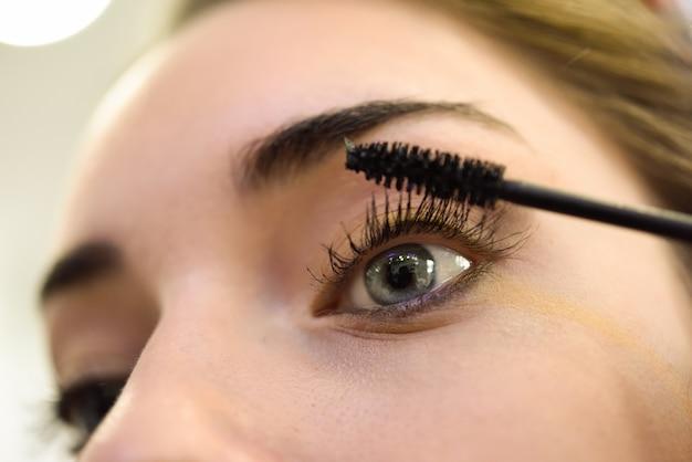 Close-up van vrouw toepassing mascara op haar wimpers