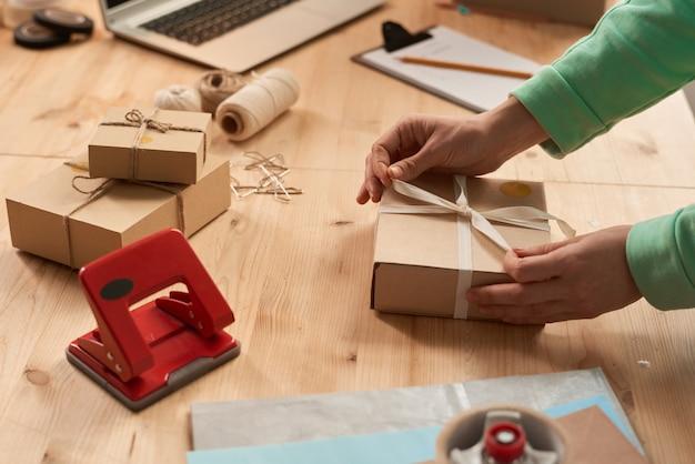 Close-up van vrouw versieren geschenkdoos met lint aan de tafel
