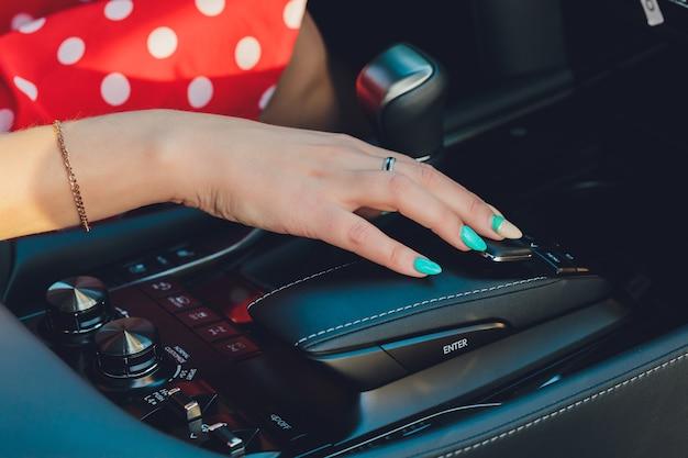 Close up van vrouw versnellingen op versnellingsbak en rijdende auto.