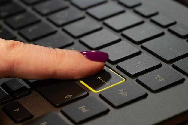 Close-up van vrouw vinger op enter-knop op toetsenbord te drukken.