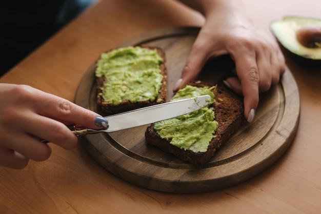 Close-up van vrouw zet guacamole of avocado uitgespreid bovenop de toast van het roggebrood op een houten bord thuis. veganistisch ontbijt