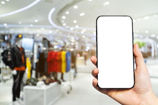 Close-up van vrouwelijk gebruik hand met smartphone met leeg leeg wit scherm in een winkel centrum
