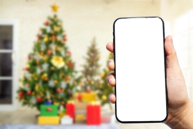 Close-up van vrouwelijk gebruik smartphone wazig beelden met kleurrijke ballen op groene kerstboom achtergrond decoratie tijdens kerstmis en nieuwjaar.