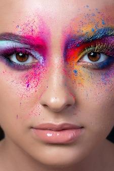 Close-up van vrouwelijk gezicht met heldere veelkleurige mode make-up. holi indian color festival geïnspireerd