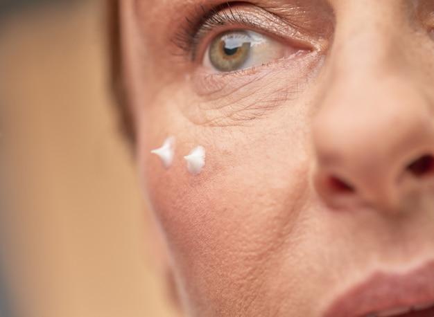 Close up van vrouwelijk gezicht met oogcrème