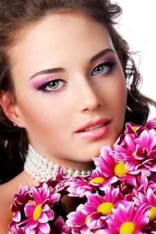 Close-up van vrouwelijk gezicht met roze chrysant. bruiloft concept.
