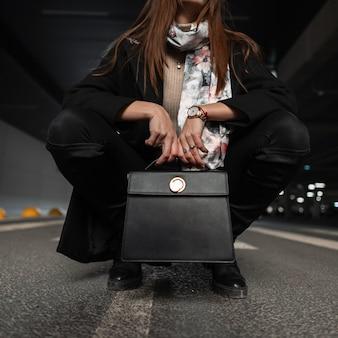 Close-up van vrouwelijk lichaam in stijlvolle zwarte seizoenskleding met vintage lederen handtas op de weg in de stad. aantrekkelijk meisje zit op asfalt in modieuze schoenen met trendy tas. lente mode.