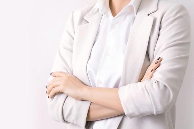 Close-up van vrouwelijk lichaam met gekruiste armen. leiderschap in het bedrijfsleven.