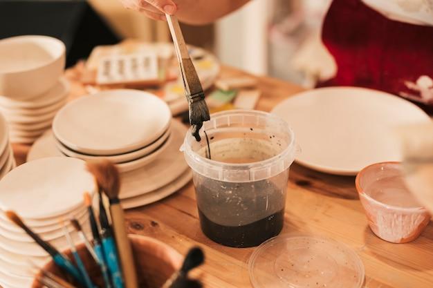 Close-up van vrouwelijke artisan die de ceramische plaat met penseel schildert