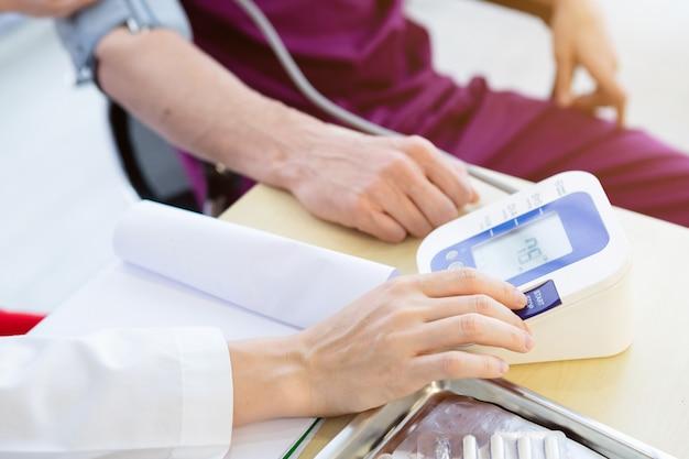 Close-up van vrouwelijke arts met het meten van de druk op de arm van een man patiënt dragen arm met digitale manometer voor een betere genezing in de kamer ziekenhuis.