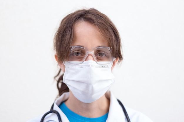 Close-up van vrouwelijke arts met wit masker en beschermende bril met verzamelde haren, witte jas en stethoscoop