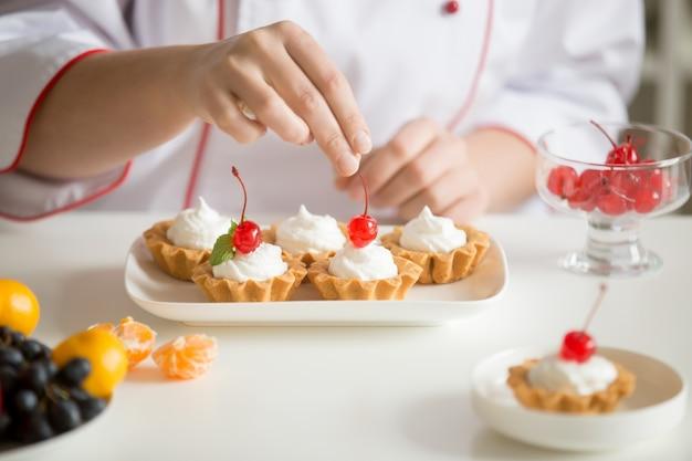 Close-up van vrouwelijke banketbakkerij handen topping custard taarten