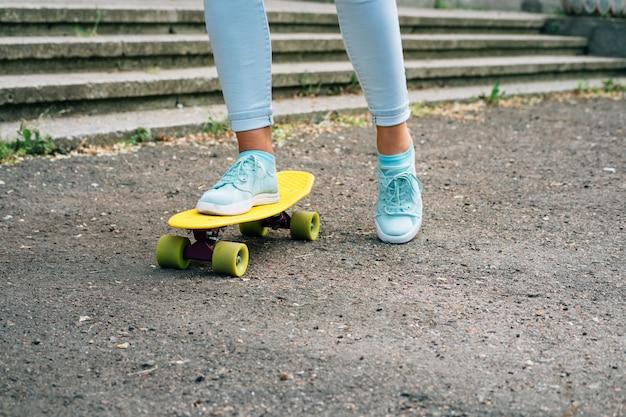 Close-up van vrouwelijke benen in jeans en sneakers rijden op een skateboard in het park