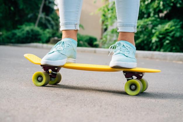 Close-up van vrouwelijke benen in jeans en tennisschoenen die zich op een geel skateboard bevinden