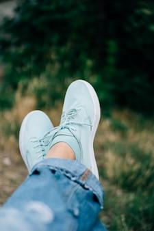 Close-up van vrouwelijke benen in jeans en tennisschoenen op een achtergrond van bomen