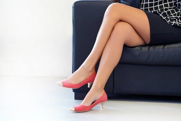 Close-up van vrouwelijke benen in schoenen die op een bank zitten. de benen van de vrouw in rode schoenen met hoge hakken, de vrouw zit ontspannen op bank, gezondheids en schoonheidsbenenconcepten.