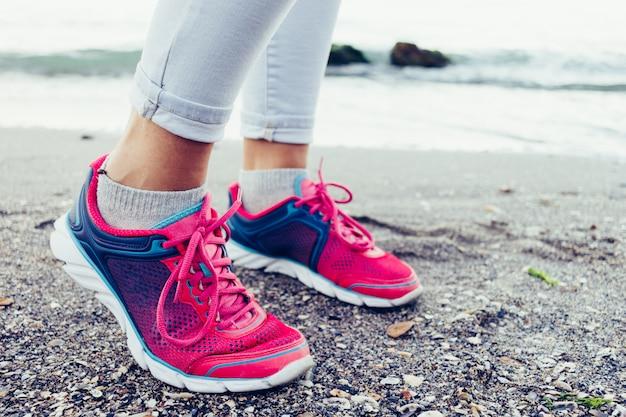 Close-up van vrouwelijke benen in sneakers en jeans op het strand in de buurt van het water