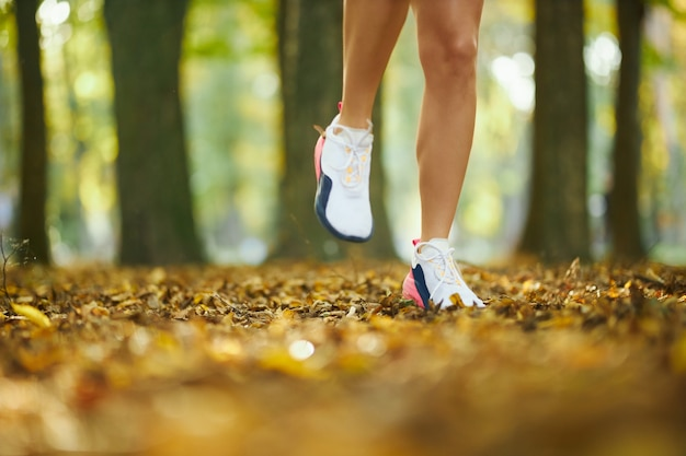 Close up van vrouwelijke benen in sport sneakers training in park
