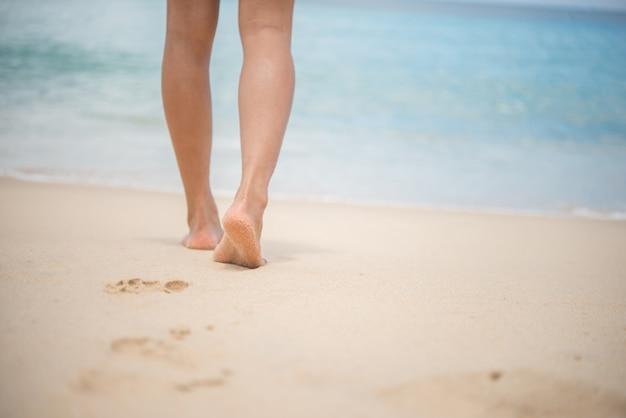 Close-up van vrouwelijke benen lopen langs het strand.