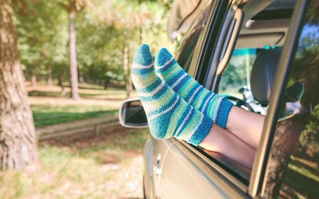 Close-up van vrouwelijke benen met blauw gestreepte sokken die over een open raamauto rusten over een aard. reis en ontspan tijdconcept.