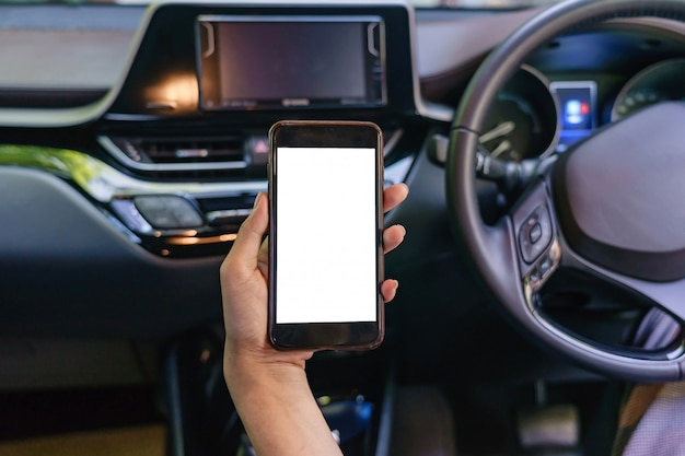 Close-up van vrouwelijke bestuurder handen met behulp van de mobiele telefoon in een auto
