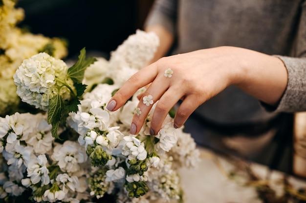 Close-up van vrouwelijke bloemisthanden die boeket maken
