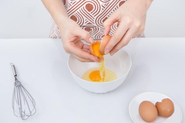 Close-up van vrouwelijke chef-kok crackende ei