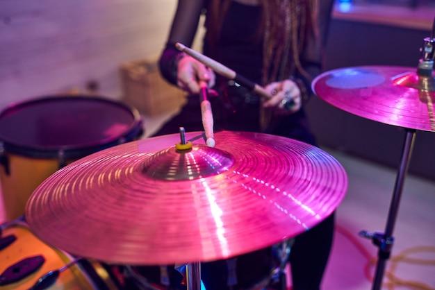 Close-up van vrouwelijke drummer die stokken gebruikt tijdens het spelen op drums tijdens het optreden