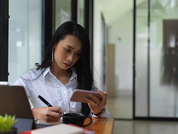 Close-up van vrouwelijke freelancer op zoek informatie op smartphone en opschrijven in kantoorruimte