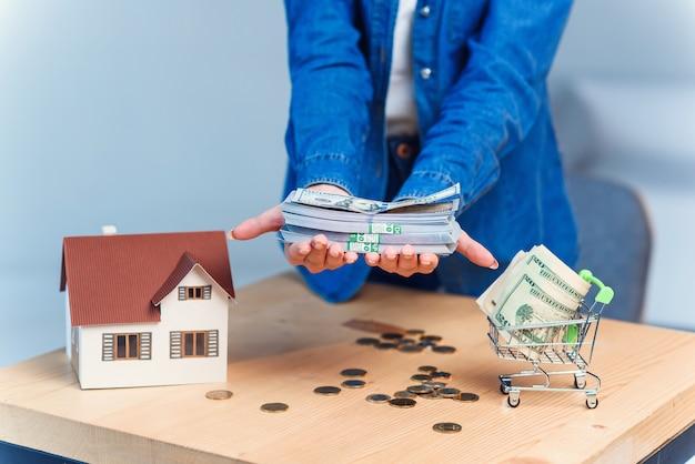 Close-up van vrouwelijke hads met een groot bedrag aan amerikaanse dollars. besparingen voor een toekomstig huis.