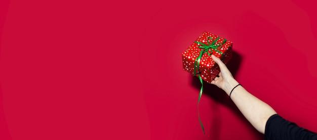 Close-up van vrouwelijke hand die een rode giftdoos houdt die op rode oppervlakte met exemplaarruimte wordt geïsoleerd.
