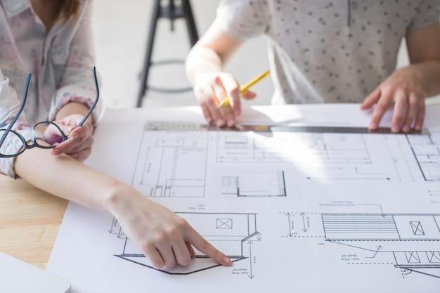 Close-up van vrouwelijke hand die op blauwdruk over lijst op het werk richt
