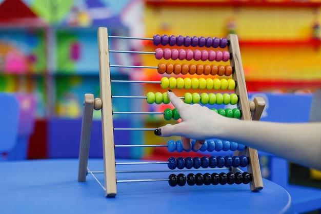 Close-up van vrouwelijke hand die op houten telraam voor aantalberekening berekent.