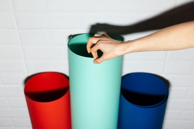 Close-up van vrouwelijke hand die papier van aqua menthe kiest, uit deze drie kleuren van weelderige lava en fantoomblauwe kleur.