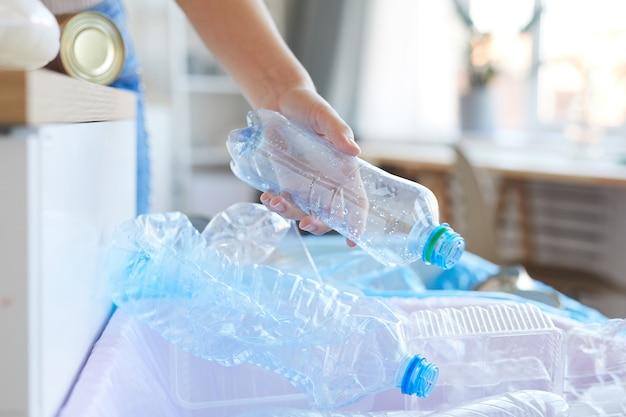 Close-up van vrouwelijke hand die plastic flessen sorteert die zij flessen in de andere bak gooit