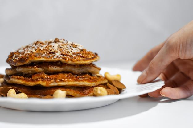 Close-up van vrouwelijke hand die witte plaat met zelfgemaakte amerikaanse veganistische pannenkoeken met cashewnoten en amandelnoten neemt.