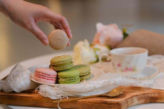 Close-up van vrouwelijke hand franse macaron plukken uit een plaat op salontafel met tae cup en decoraties